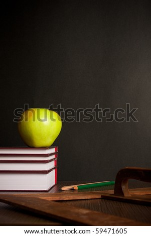 School books with apple on desk - stock photo
