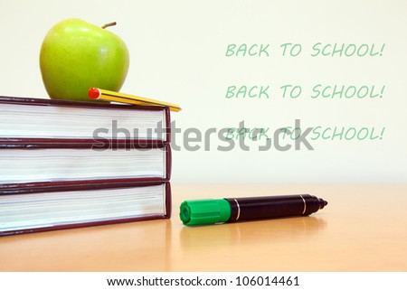 School books with apple on desk at modern classroom - stock photo
