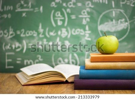 School books with apple on desk over green  school board background - stock photo