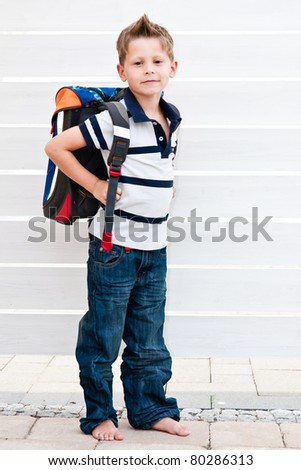 School boy carrying his school bag standing front of white fence - stock photo