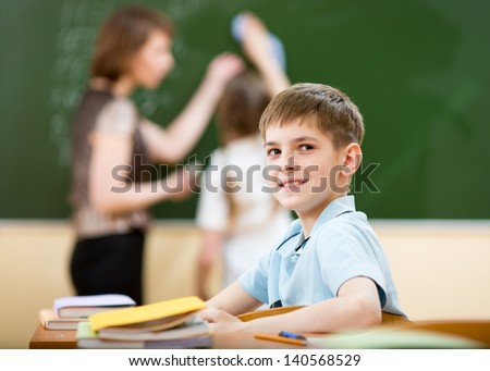 School boy in classroom at lesson - stock photo