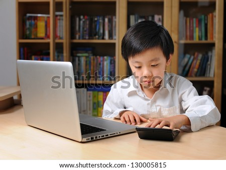 School boy in front of laptop computer and making calculations on calculator - stock photo
