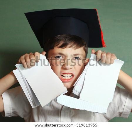 school boy in graduation cap rebel against hard learning - stock photo