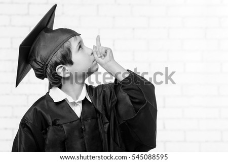 School boy in graduation dress points up with his finger.