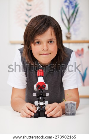 School boy in science class with microscope and young plant - study biology - stock photo