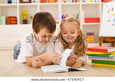 School boy laying on the floor teaching and showing her sister how to read