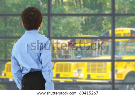 School boy looking out window at buses in parking lot. - stock photo