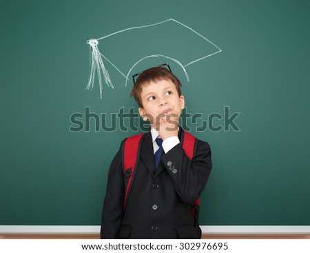school boy portrait with academic cap on board background - stock photo