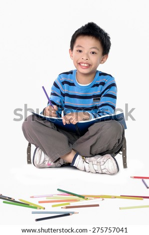 School boy sitting and writing in notebook - stock photo