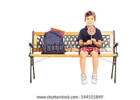School boy sitting on a bench and holding a candy lollipop isolated on white background - stock photo