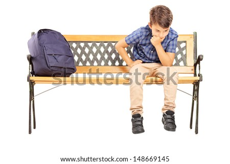 School boy sitting on a bench and thinking, isolated on white background  - stock photo
