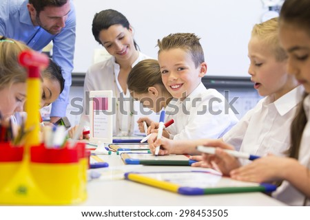 School boy smiles at the camera as he sits at his desk while working. - stock photo