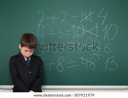 School boy solve math on the school board  - stock photo
