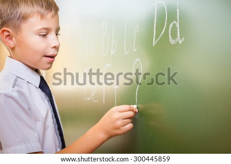 School boy writes English alphabet with chalk on a blackboard in school classroom. He does not know continuation of the alphabet and wrote a question mark. - stock photo