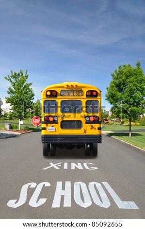 School Bus and Crossing Sign on Suburban Neighborhood Street on Sunny Day - stock photo