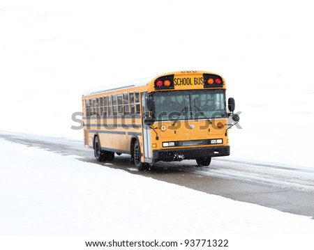 School bus driving in the winter on rural road - stock photo