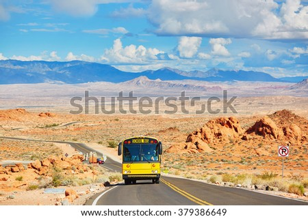 School bus driving on winding road in Valley of the Fire national park in Nevada, USA - stock photo