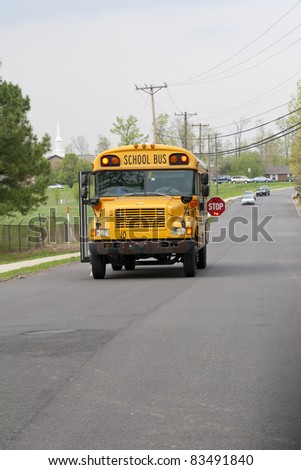 School bus dropping of children after school, traffic staying well back - stock photo