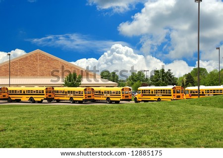 School bus lineup in front of the county school on a warm spring day. - stock photo