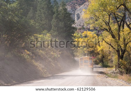 School bus on a rural dirt road in autumn - stock photo