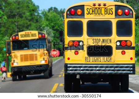 school bus on rural road picking up children - stock photo