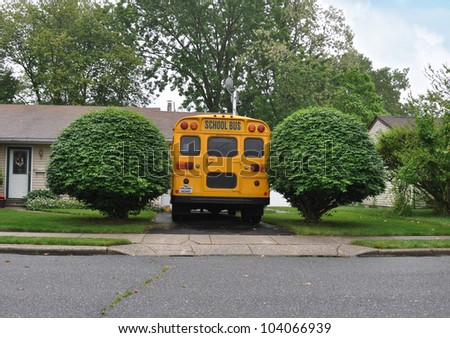 School Bus Parked in Driveway of Suburban Home Rainy Day - stock photo