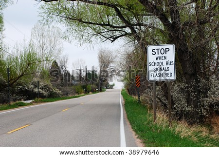 School bus signals flash red sign at the side of a road in a rural area - stock photo