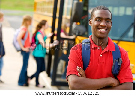 School Bus: Smiling Teen Student with Others Behind - stock photo