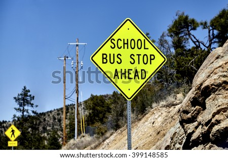 School Bus Stop Ahead sign with pedestrian crossing sign in background and mountain terrain - stock photo