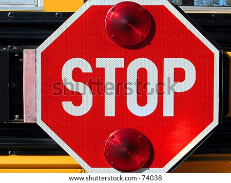 School bus stop sign on the side of the bus that flashes when the bus stops.