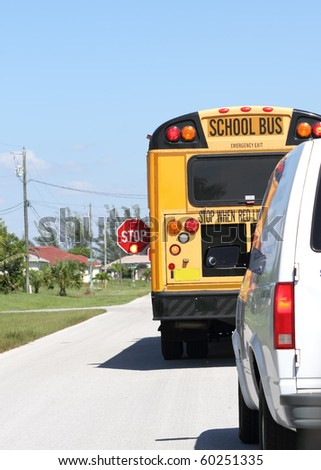 School Bus stopped to get kids to the school - stock photo