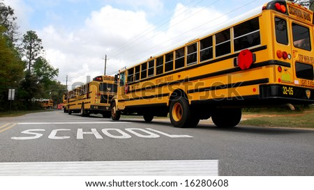 School buses lined up at school crosswalk - stock photo