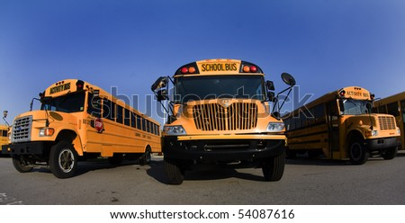 School busses sit in a parking lot - stock photo