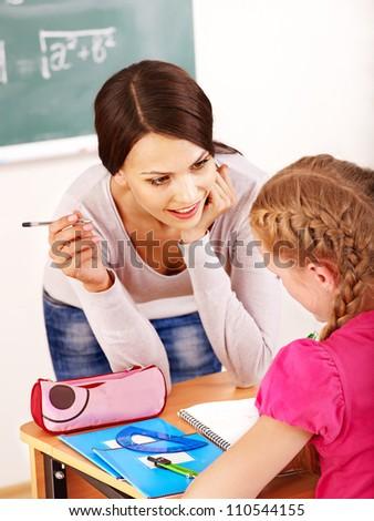 School child with teacher near blackboard. - stock photo