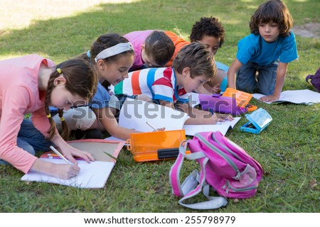 School children doing homework on grass on a sunny day