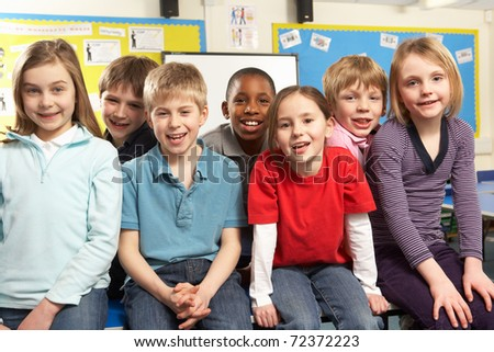 School Children In Classroom Smiling - stock photo