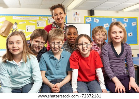 School Children In Classroom With Teacher - stock photo