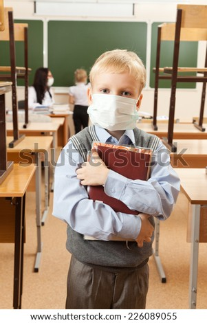 School children in medical face mask are learning in the half empty classroom during epidemic of flu. - stock photo
