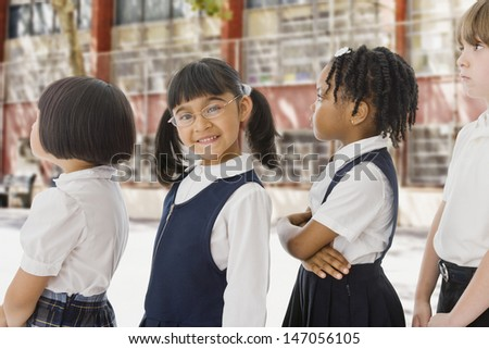 School children in uniforms in a row outdoors - stock photo