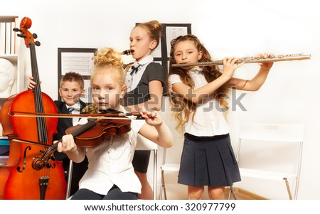 School children playing musical instruments together during their concert in school - stock photo