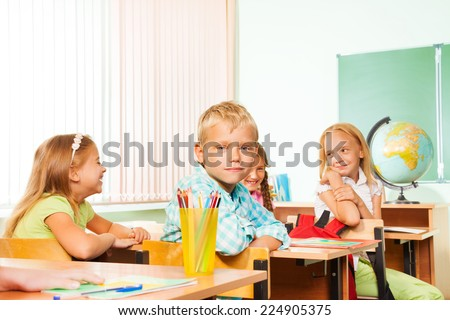 School children sitting at tables during geography - stock photo