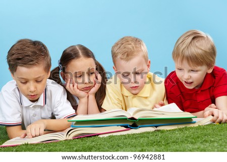 School children studying books lying on the grass