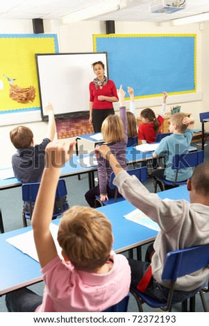 School Children Studying In Classroom With Teacher - stock photo
