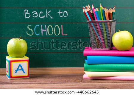 School concept, apples, books and colored pencils on the chalkboard with back to school written background