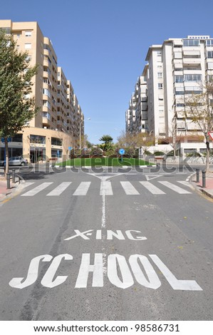 School Crossing Traffic sign Pedestrian Crosswalk on street of Urban City Highrise Residential area - stock photo