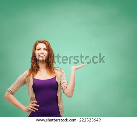 school, education, advertising and people concept - smiling teenage girl in casual clothes holding something on her palm over green board background - stock photo