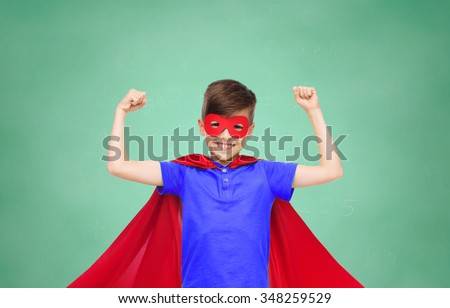 school, education, childhood, power and people concept - happy boy in red super hero cape and mask showing fists over green chalk board background - stock photo