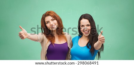 school, education, friendship, gesture and happy people concept - two smiling student girls or young women showing thumbs up over green chalk board background - stock photo