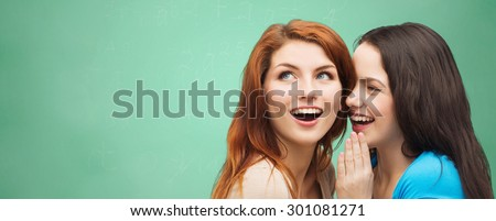 school, education, friendship, secrecy and people concept - two smiling student girls or young women whispering gossip over green chalk board background