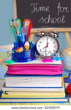 school equipment and retro alarm clock on the desk in the classroom - stock photo